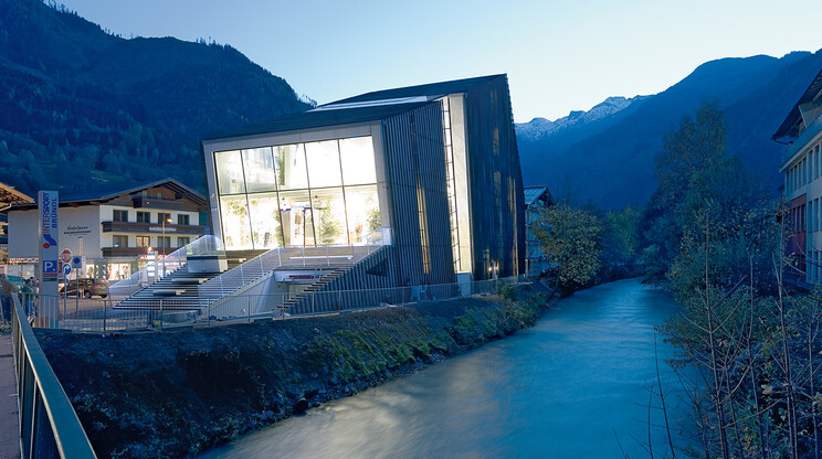 New construction - sports and lifestyle house - alpine sports store - Bründl Kaprun - facade overview - building next to river - evening light