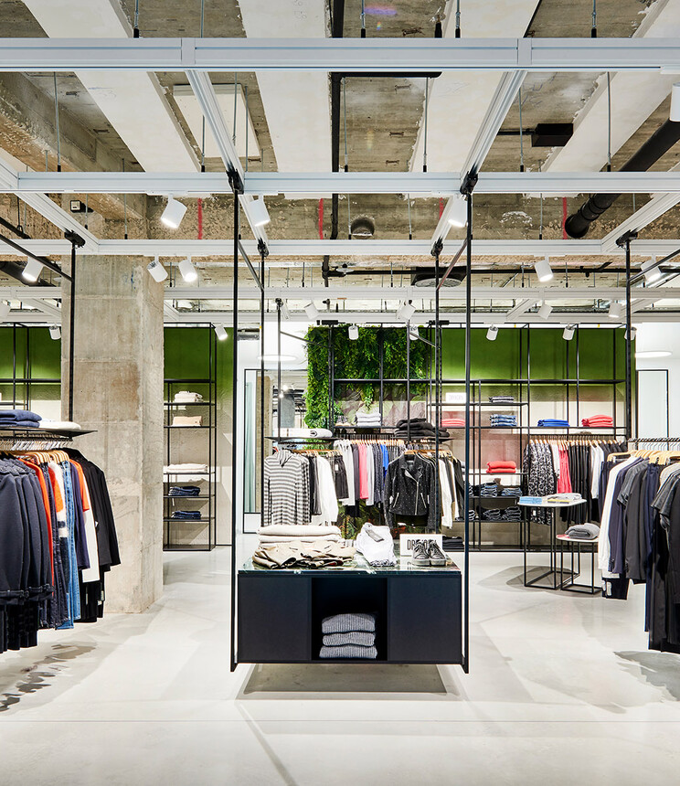 young womens fashion store - complete redesign - Kaiser Freiburg - interior architecture - wide angle store overview - green wall - steel racks