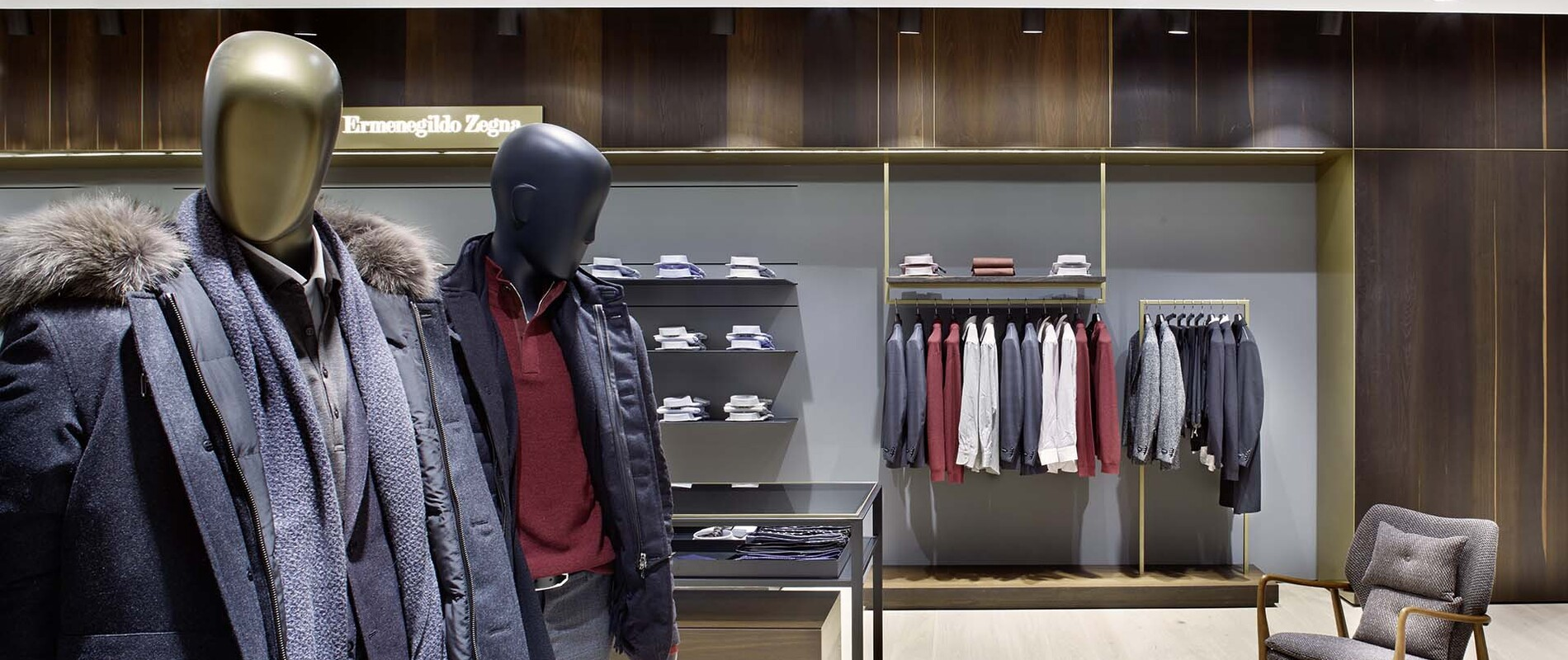 mens fashion store - conception- design - realization - Mode Reischmann Ulm - mannequins in front of wooden clothes display wall - lounge chair